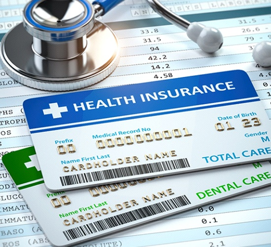 Health and dental insurance cards next to stethoscope