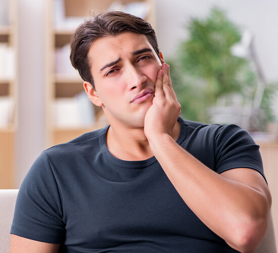 Man in need of tooth extraction holding jaw