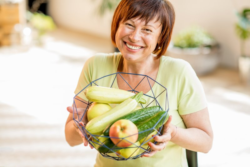 a middle-aged woman holding a basket of vegetables and fruit while wearing dental implants in Edison