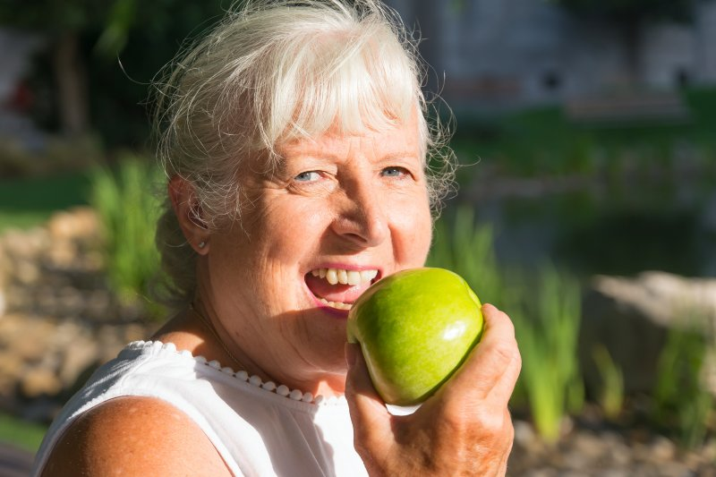 older woman with dentures eating apple outside during summer